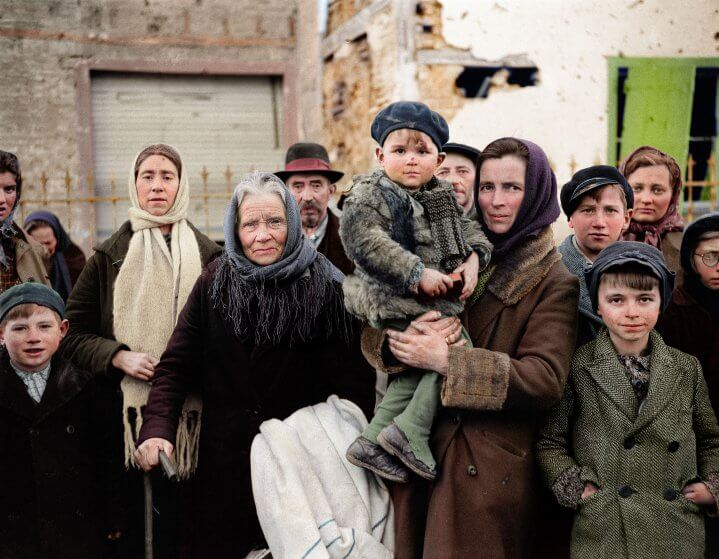 Grim-faced refugees stand in a group on a street in La Gleize, Belgium on Jan. 2, 1945. They are waiting to be transported from the war-torn town after its recapture by American forces during the German thrust into the Belgium-Luxembourg salient. (AP Photo/Peter J. Carroll)